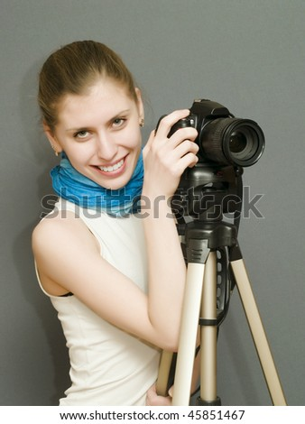 pretty girl holding a camera in the hands - stock photo
