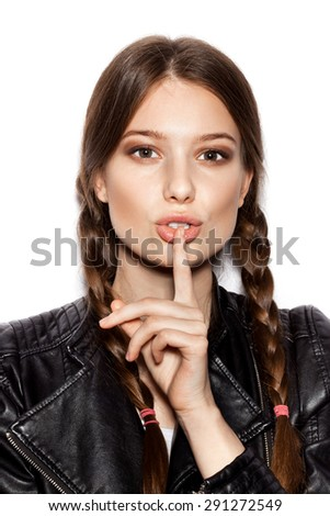 pretty girl holding a finger on her lips - stock photo