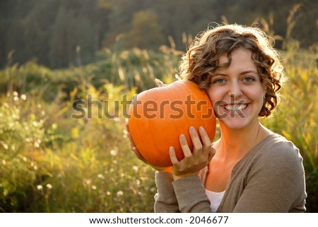 Pretty girl holding a pumpkin to her cheek - stock photo