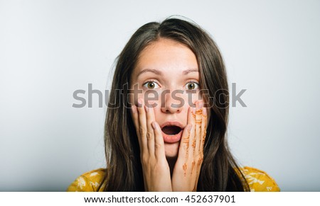 Pretty girl holding a shocked and surprised, isolated on a gray background