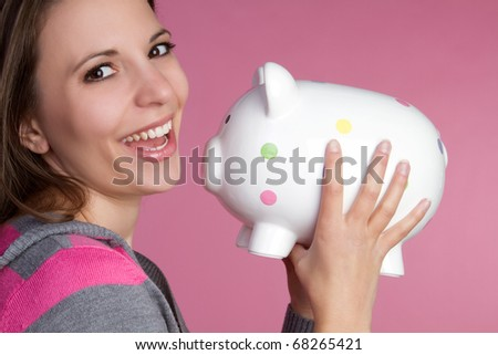 Pretty girl holding piggy bank - stock photo