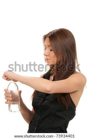 Pretty girl holding purity mineral sparkling bottle of potable water in hand and trying to open a cap on a white background - stock photo