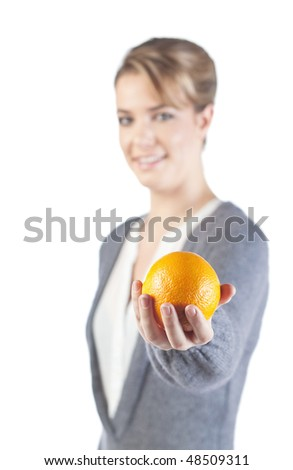 Pretty girl holds an orange in her hand; isolated on white background; only orange and hand is in focus - stock photo