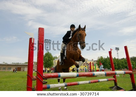 pretty girl horse jump equestrian and audience - stock photo