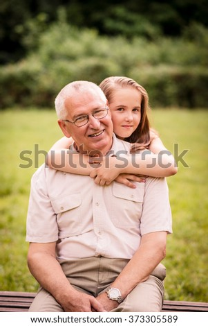 Pretty girl hugging her happy grandfather - outdor in nature - stock photo