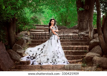 Pretty girl in a beautiful flying dress posing against the backdrop of lakes and rocks. .fashionable toning.creative colors.Fairy princess walking in the desert.Girl with beautiful hair and clean skin - stock photo