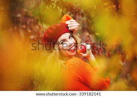 Pretty girl in a beret and a sweater in autumn park, holding a ripe apple and smiling. Girl model. The girl white smile. The concept of healthy teeth.