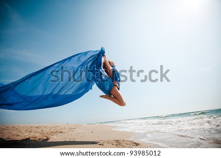 pretty girl in a blue cloth jumping on the beach - stock photo