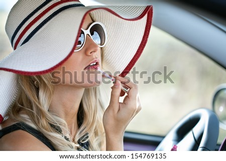 Pretty girl in a car. Cute blond woman makes up lips in the car  - stock photo