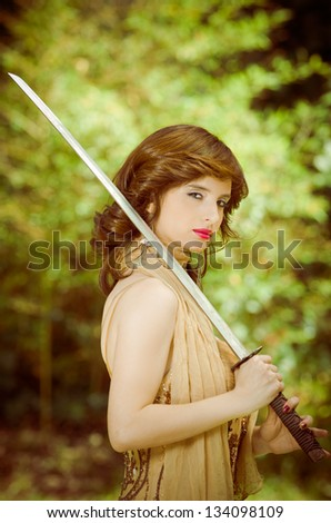 Pretty girl in a dress with vintage sword outdoors - stock photo