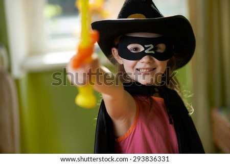 Pretty girl in a superhero suit raises his sword up - stock photo