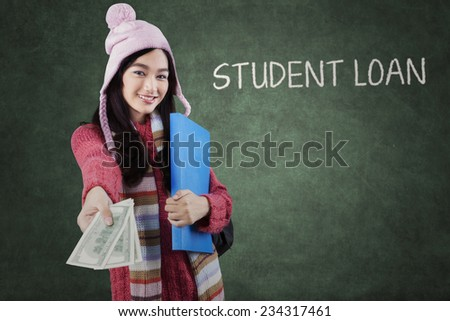 Pretty girl in a winter fashion offering money dollars for student loan in the classroom - stock photo