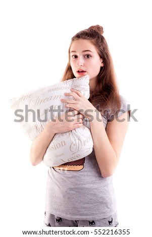 Pretty girl in bedclothes hold pillow and make surprise face isolated