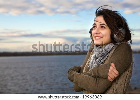 Pretty girl in big professional headphones on the sky background.