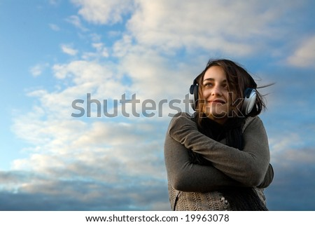 Pretty girl in big professional headphones on the sky background. - stock photo