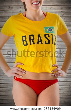 Pretty girl in bikini and brasil tshirt against wooden planks background - stock photo