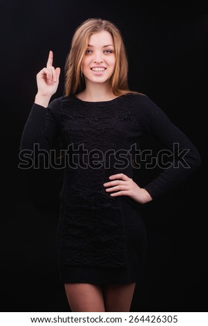 Pretty girl in black dress pose in studio. Point up gesture - stock photo
