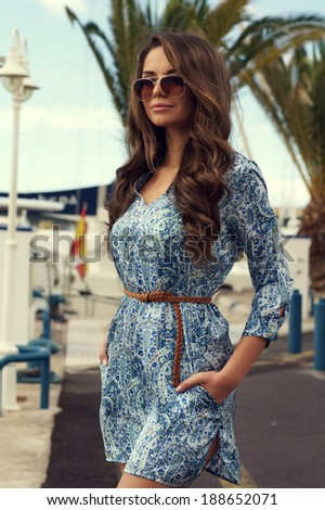 Pretty girl in blue summer dress walking along the street - stock photo