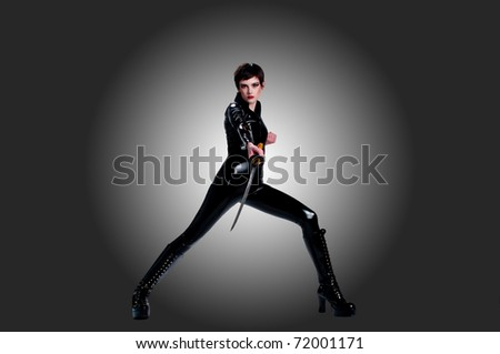 Pretty girl in bodysuit and boots in martial arts stance - stock photo