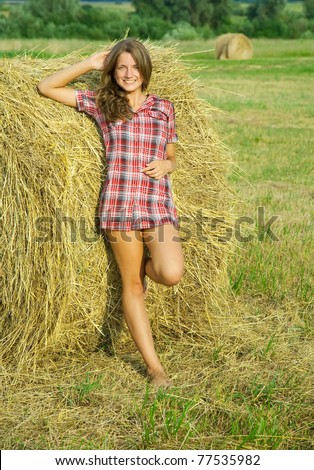 Pretty girl in checked dress resting on straw bale - stock photo