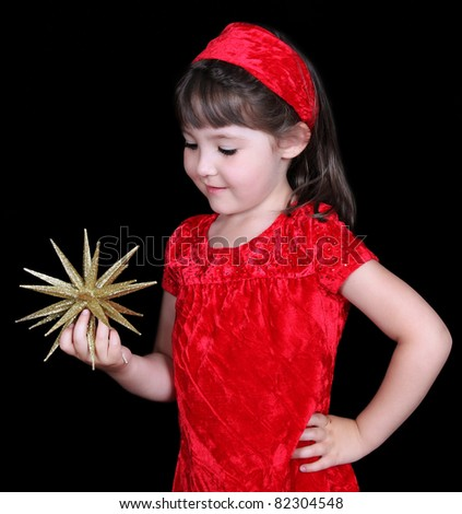 pretty girl in christmas dress holding gold star. isolated on black