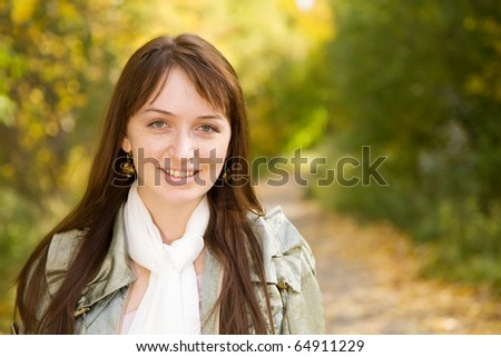 Pretty girl in cloak at autumn park - stock photo