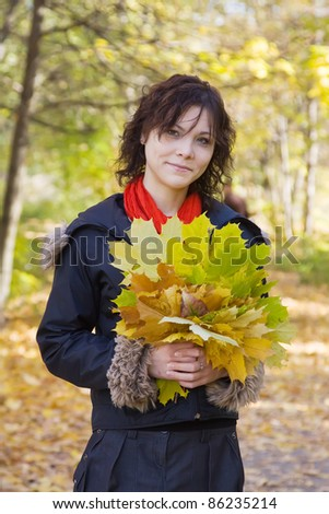 Pretty girl in coat at autumn park - stock photo