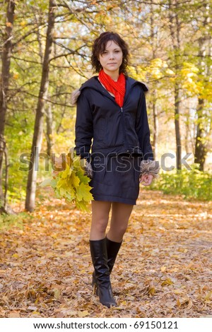 Pretty girl in coat walking outdoors in autumn - stock photo