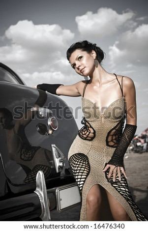 Pretty girl in exclusive woolen dress near the vintage car. - stock photo