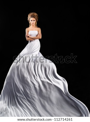 Pretty girl in fluttering white dress - stock photo
