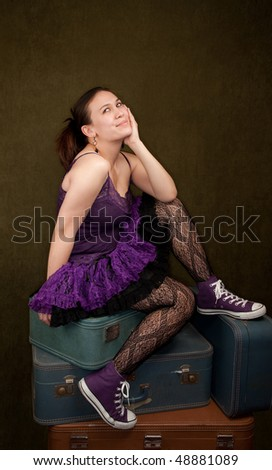 Pretty girl in funky purple outfit on green background - stock photo