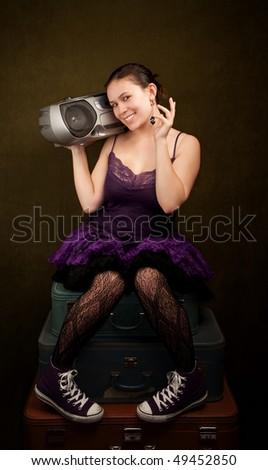 Pretty girl in funky purple outfit on green background with big radio - stock photo