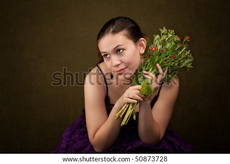Pretty girl in funky purple outfit on green background with flowers - stock photo