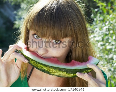 pretty girl in green dress eating watermelon - stock photo