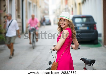 Pretty girl in hat and pink dress riding a bicycle at Italian streets