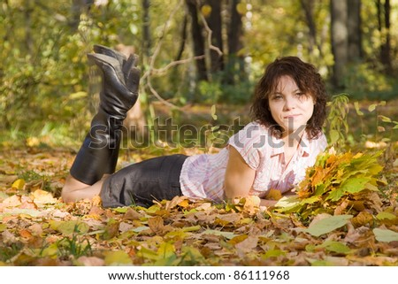 Pretty girl in knee-boots  lying in autumn park - stock photo
