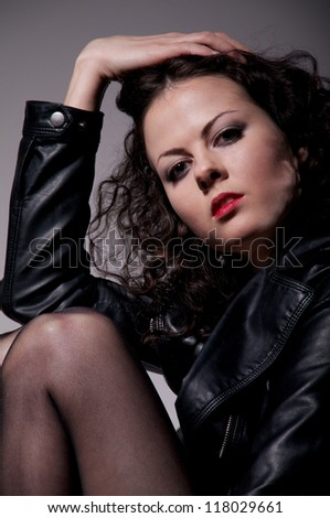 pretty girl in leather jacket and stockings on gray background