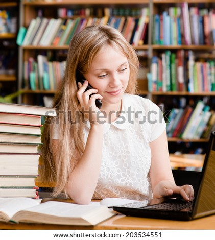 pretty girl in library typing on laptop and talking on the phone