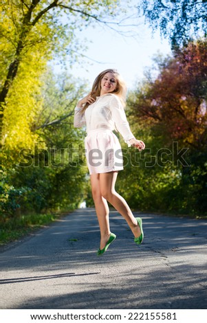 pretty girl in mini dress jumping high and happy smiling on blue sky outdoors copy space background portrait - stock photo