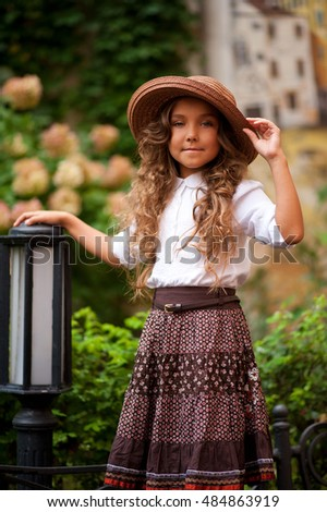 Pretty girl in old-style in the courtyard in summer
