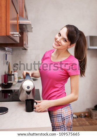 Pretty girl in pajamas pours water from the kettle in the kitchen - stock photo