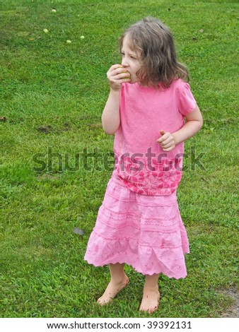 pretty girl in pink eats an apple on a vivid green lawn