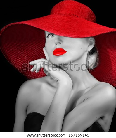 pretty girl in red hat with red lipstick on lips looking at camera - stock photo