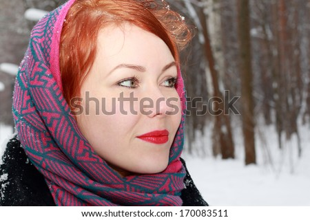 Pretty girl in red kerchief looks away outdoor at winter day in park