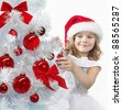 pretty girl in red santa's hat decorating christmas tree - stock photo