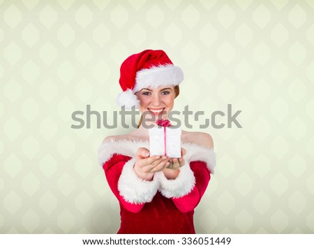 Pretty girl in santa costume holding gift box against room with wooden floor - stock photo