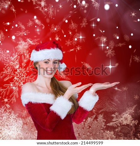 Pretty girl in santa costume holding hand out against red snow flake pattern design