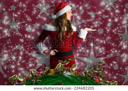 Pretty girl in santa costume holding hand out against snowflake wallpaper pattern