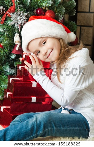 Pretty girl in Santa hat lying on the gifts near christmas tree