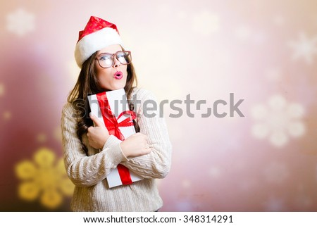 Pretty girl in Santa hat surprised holding giftbox with snowflakes